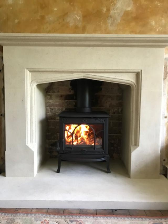 Jotul F100 stove in stone fire surround
