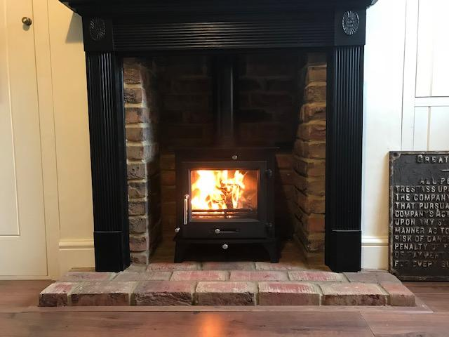Clock wood stove with timber fire surround