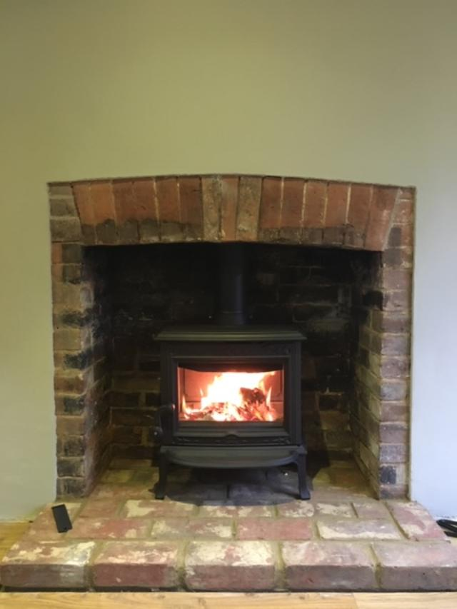 Jotul multi-fuel stove in fireplace