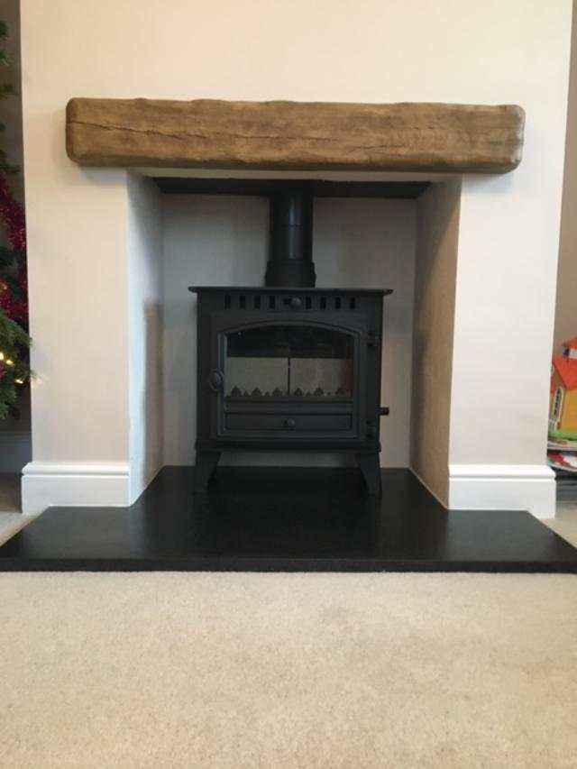 Arada wood burning stove with wooden beam above